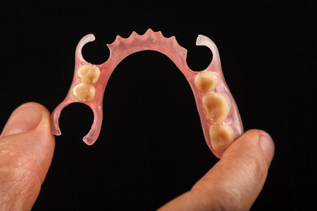 Dental prosthesis in the hand of the dentist. Close-up on a black background
