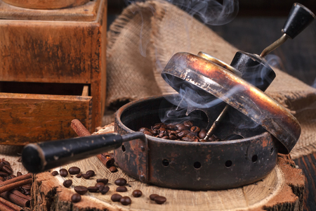 The device for roasting coffee beans, an old hand grinder. Smoky roast coffee on a wooden stand. Studio lighting.