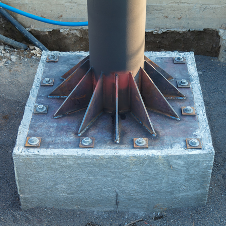 Installation and brewing of metal kerchiefs to strengthen the metal pipe. The pipe is mounted on a metal plate, which is fixed in concrete.