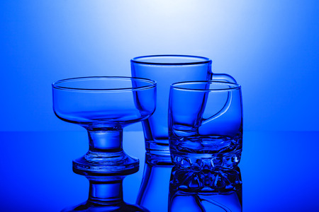 Transparent glass glasses stand on a glossy surface on a blue background Stock Photo