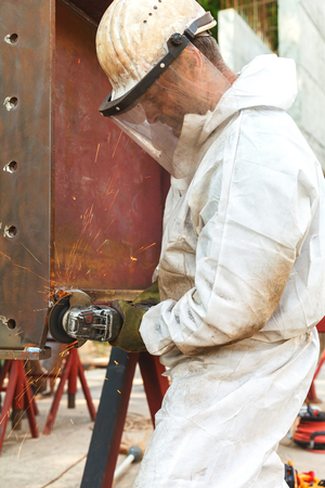 An employee in white overalls and a protective mask processes with electric flexion a metal structure