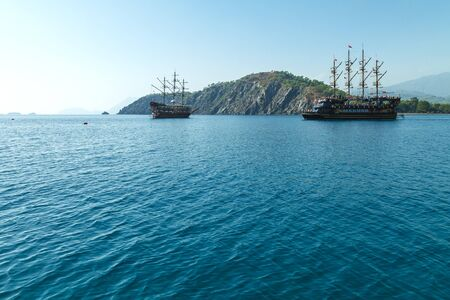 Pleasure pirate ship with tourists sailing in the Mediterranean Sea along the coastline at the foot of the mountain