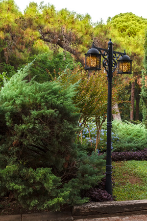 Beautiful metal street lamp with yellow lamps on a background of green trees and bushes on a sunny day