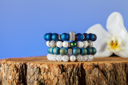 Exquisite women's bracelets made of natural stones, agate and sugar quartz with accessories that are encrusted with cubic zirconias. Close-up. Studio lighting