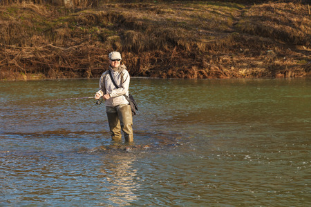 A young attractive woman is fishing with a spinning standing in a river on a clear spring sunny day.