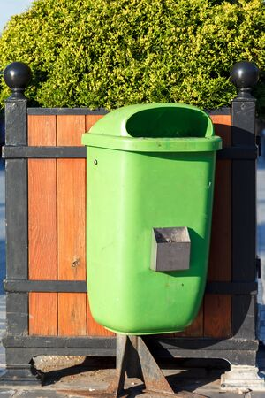 A green plastic wastebasket with a faded color mounted on a partially destroyed rusty metal stand with a concrete foundation in a public park. Natural light, sunny. Vertical frame
