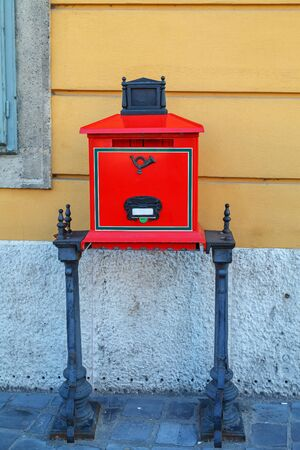 A beautiful retro red mailbox on metal coasters is installed on a street of Budapest, Hungary near the yellow wall of the house.