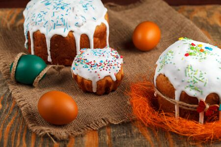 Fresh Easter cake, baked at home and decorated with sweet icing. Colored boiled eggs lie on the table as an element of the Easter holiday. Artificial lighting
