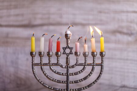 Jewish holiday Hanukkah. Menorah with candles for Hanukkah on a light wooden background. Front view