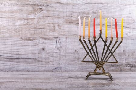 Jewish holiday Hanukkah. Menorah with candles on a light, wooden background. The concept of the Jewish holiday of Hanukkah. Front view