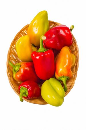 str: colored peppers in a straw basket on a white background