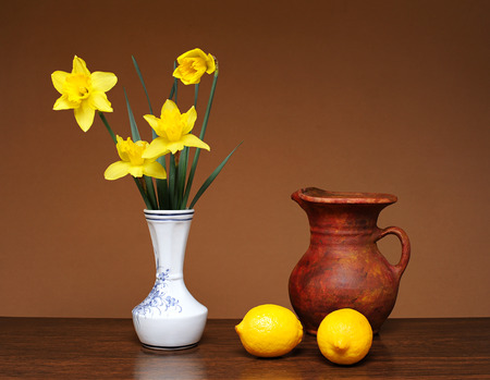 gusto: Lemon and flowers in a vase on a wodden table Stock Photo