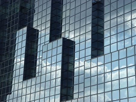 A glass building by the side of the river Thames showing a reflection of the sky
