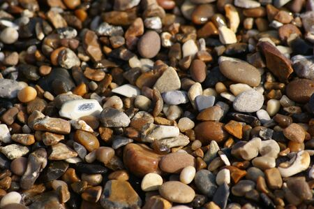 Lots of coloured small stones and pebbles on a beach