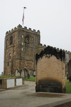 A weathered gravestone standing outside of St Marys Church in Whitby, England