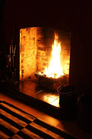 A wood burning fire in a darkened room