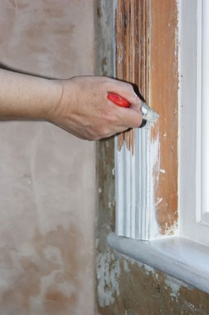 Painting a window frame with white undercoat