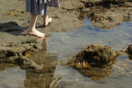A woman on the beach walking besides a rock pool