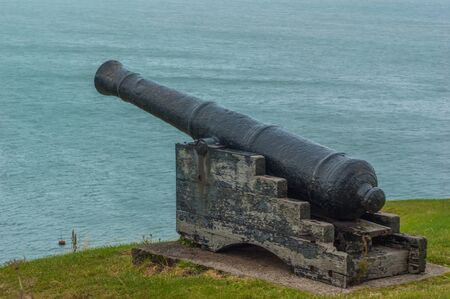 A cannon pointing out over the sea