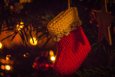 Handmade knitted Christmas stocking decoration hanging in tree Stock Photo