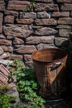 A rusty bin in front of a stone wall in portrait orientation Stock Photo