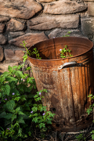A rusty bin with weeds growing in it in front of a stone wall Stock Photo