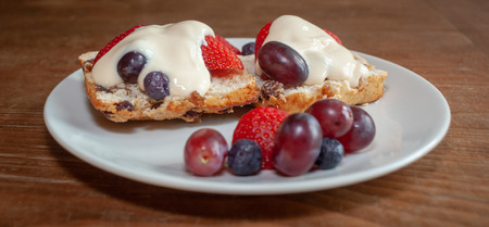 Fruited scone and cream with strawberries, grapes and blueberries on a white plate on wooden table from side, panorama format