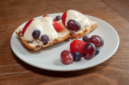 Fruited scone and cream with strawberries, grapes and blueberries on a white plate on wooden table from side