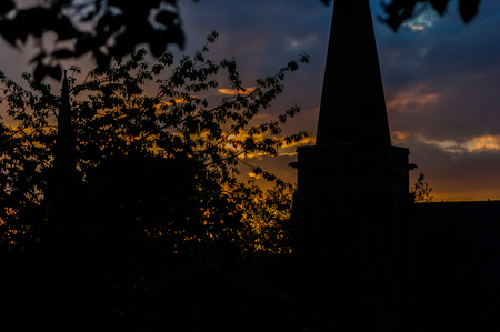 Sunset with a silhouetted church steeple and tree, landscape orientation Stock Photo