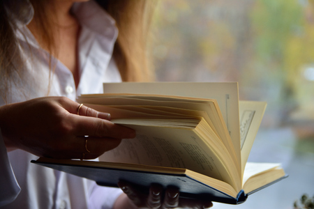 The girl turns the pages of the book Stock Photo