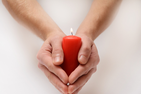 Red candle in loving hands Stock Photo