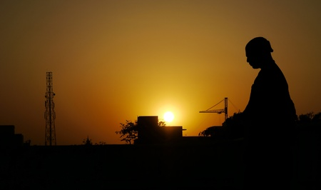 A devotee in silhouette sits on a roof-top, meditating, in an orange sunset in Vrindavana, India