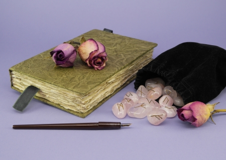 A green journal with dried roses sits next to a black velvet bag of rune stones with a calligraphy pen on a purple background