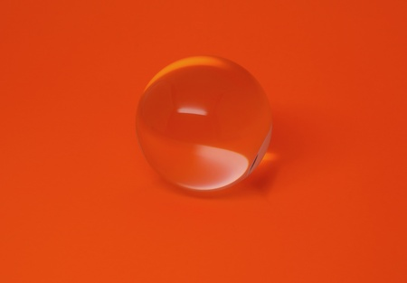 A clear, crystal ball sits on a bright, vibrant orange background