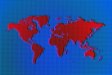 A macro shot of a red world map graphic on a computer screen with a blue background