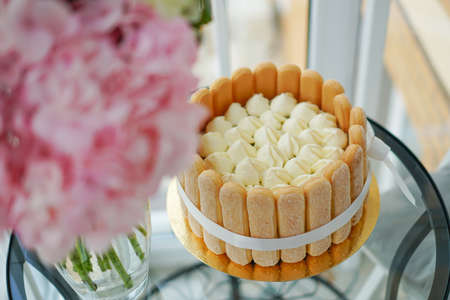 Cooking and decorating Tiramisu cake at home by a master. Sponge cake with flowers and cookies