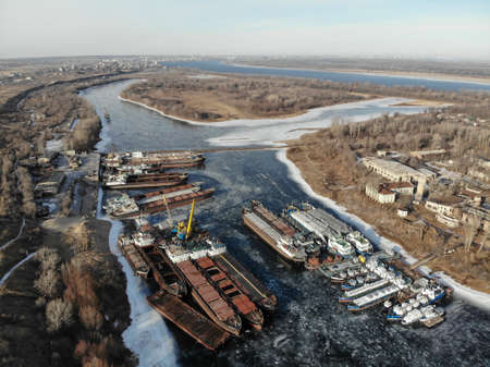Wintering ships on a frozen river. There are many ships at the pier. Volgograd. Russia