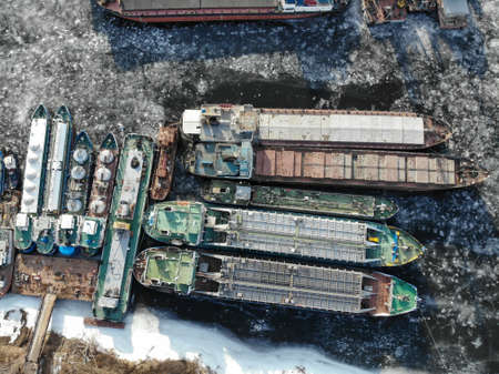 Volga river. Wintering ships on a frozen river. There are many ships at the pier. Volgograd. Russia