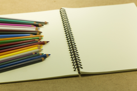 drawing pad: color pencils on a drawing pad on wood background