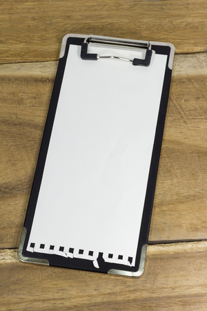 mini clipboard with blank paper on wooden background