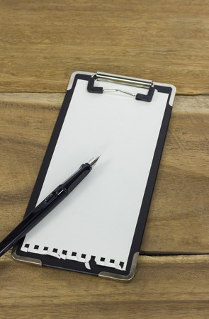 mini clipboard with blank paper and a pen on wooden background