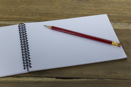 red pencil and drawing pad on wood background Stock Photo