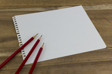red pencil and drawing paper on wood background Stock Photo