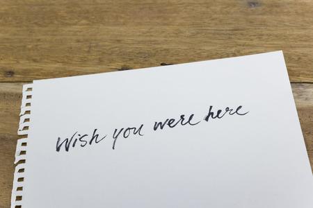 wish you were here hand written on white paper Stock Photo