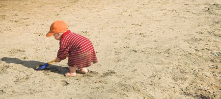 Small boy playing with shovel in sand (no face showing)