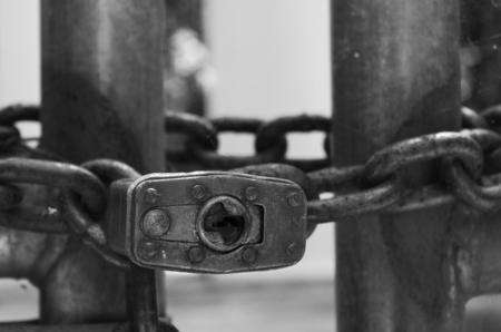 Close up of a pad lock and chain on a fence.