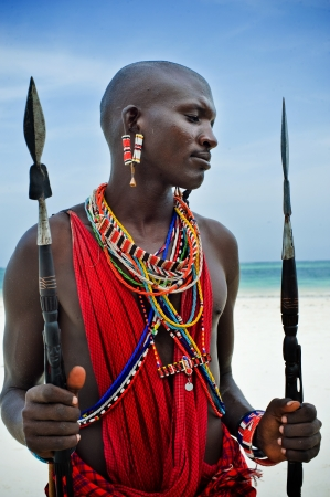 Maasai sitting by the ocean on the beach photo