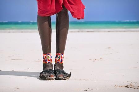 tribu: Pies y zapatos masai en la playa del océano