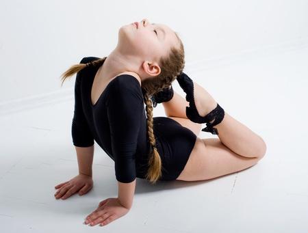 small pretty girl doing gymnastics over white background Standard-Bild