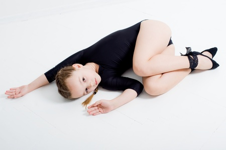small pretty girl doing gymnastics over white background photo